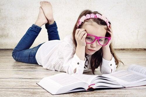 Mädchen mit großer Brille liest zwei Bücher