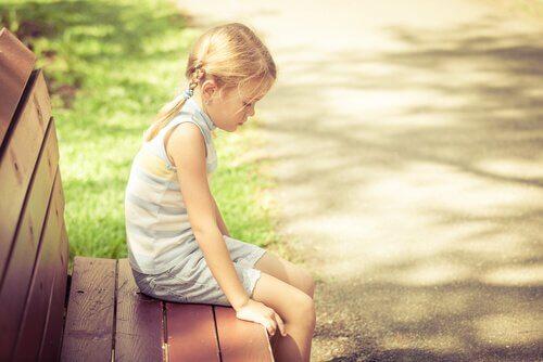 Trauriges Mädchen auf einer Parkbank