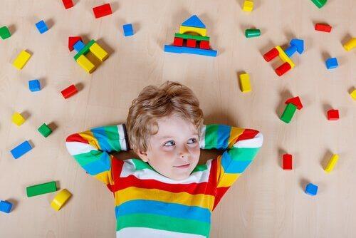 Junge auf dem Boden, von bunten Bausteinen umgeben