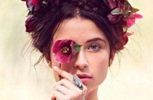 Wahrheiten über das Leben - Frau hält sich eine Blume vor ihr Auge, um sich der Wahrheit nicht stellen zu müssen