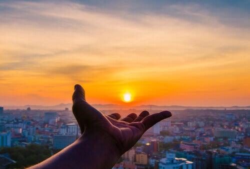 Hand hält untergehende Sonne über einer Stadt
