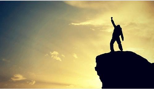 Erfolg: Person auf einem Felsen streckt ihren Arm gen Himmel.