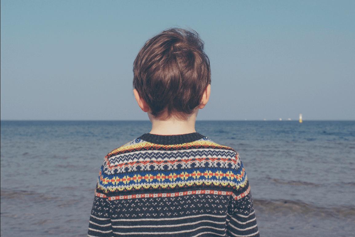 Ein Junge im Strickpulli steht am Meer und dreht uns den Rücken zu.