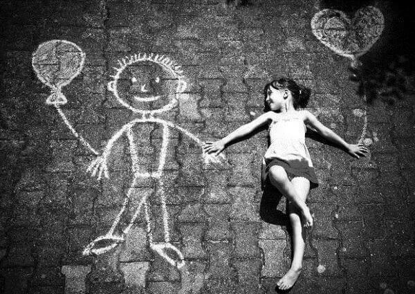 Ein Mädchen liegt auf dem Boden und hält Händchen mit einem gezeichneten Kreidemännchen.