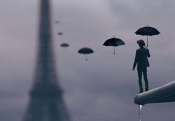 Mann mit Schirmen vor dem Eiffelturm