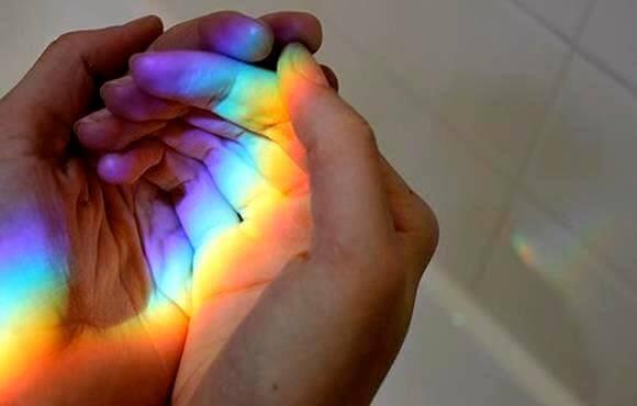 Prisma wirft Regenbogenfarben in die hohle Hand