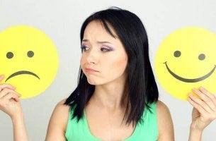Frau schaut zwischen glücklichem und traurigem Smiley hin und her.