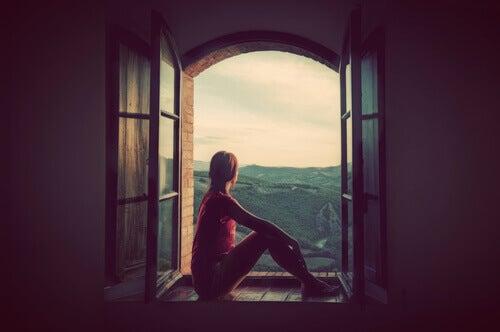 Frau sitzt am offenen Fenster
