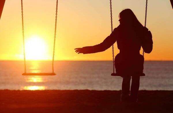 Frau sitzt bei Sonnenuntergang allein auf einer Schaukel am Wasser