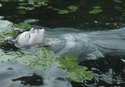 Eine Frau liegt auf dem Rücken in einem Fluss