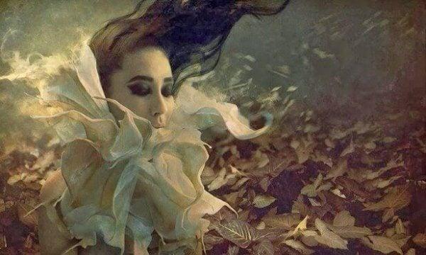 Eine Frau mit weißem Blütenkragen steht in windiger Atmosphäre auf einem Blätterteppich.