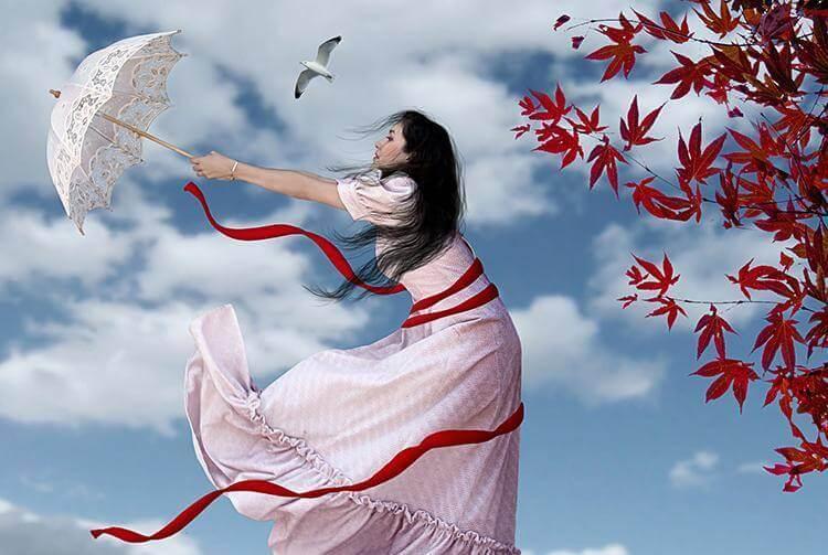 Eine Frau mit einem Schirm vor einem roten Ahorn