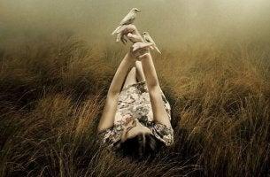 Frau mit Tauben auf den Händen liegt im Feld