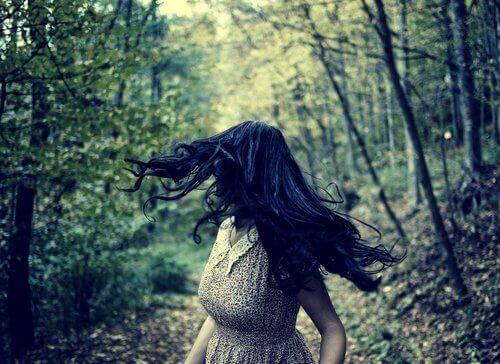 Frau mit Verfolgungsangst dreht sich im Wald nach hinten um.