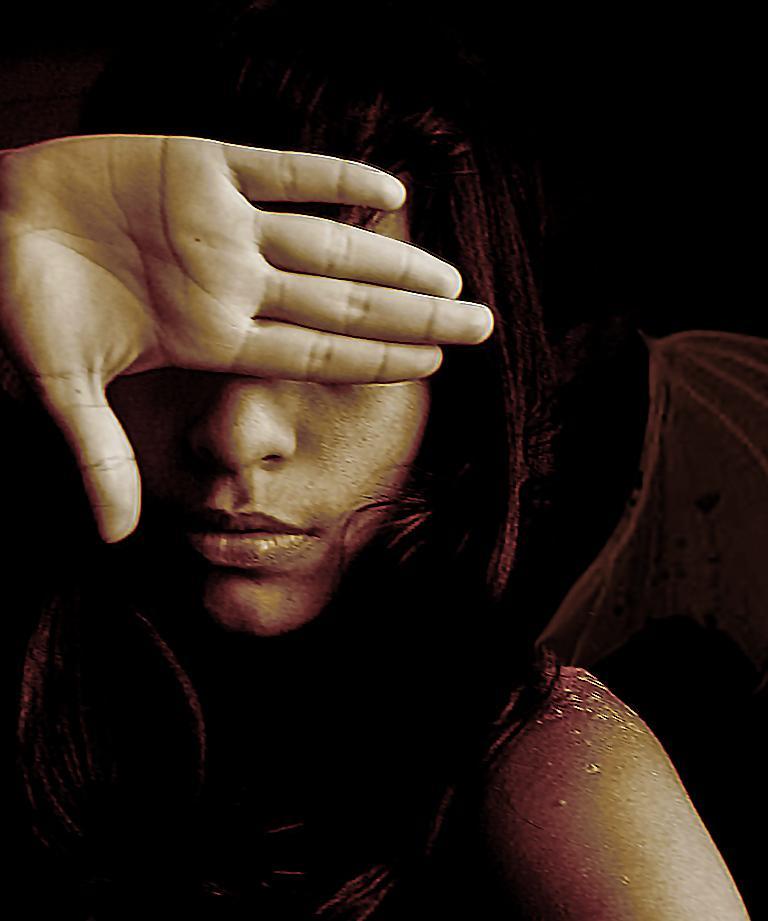 Frau verdeckt mit ihrer Hand ihr Gesicht