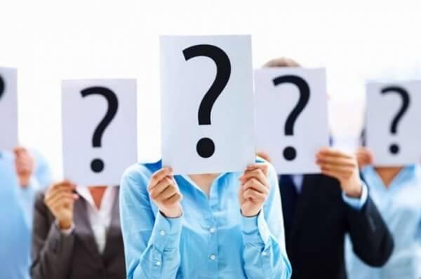 Fünf Menschen verdecken ihr Gesicht hinter hochgehaltenen weißen Schildern, auf den ein schwarzes Fragezeichen prangt.