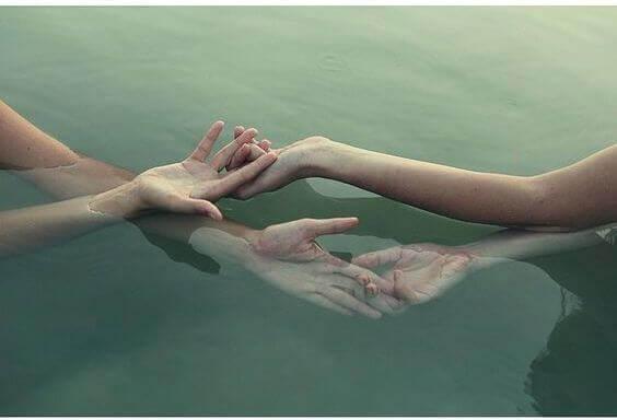 Eine sanfte Berührung der Hände zweier Personen im Wasser