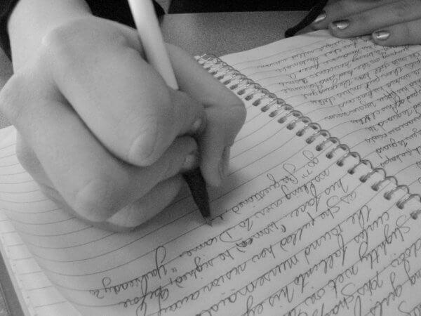 Eine Frau verfasst einen handschriftllichen Eintrag in ein liniertes Ringbuch.