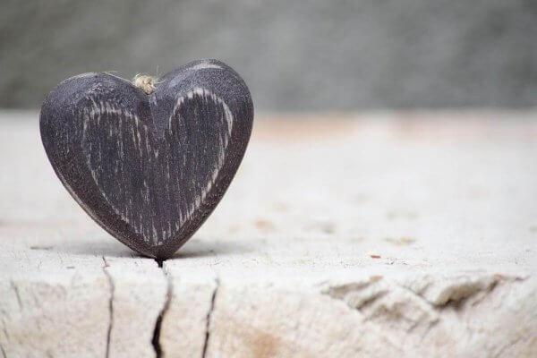 Das Gesetz der Anziehung - Kleines Herz aus Holz steckt in einem Holzspalt.