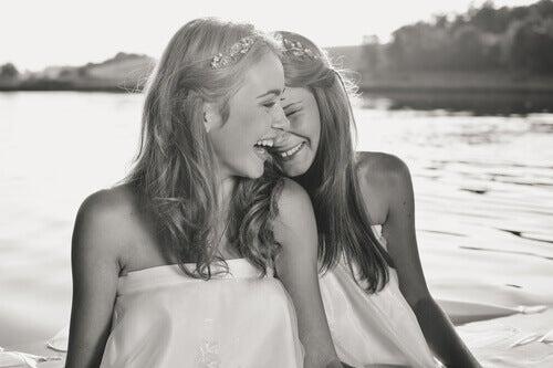 Menschen, die lachen können - zwei Freundinnen am Strand