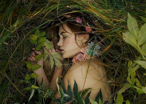 Eine Frau schläft umgeben von Pflanzen