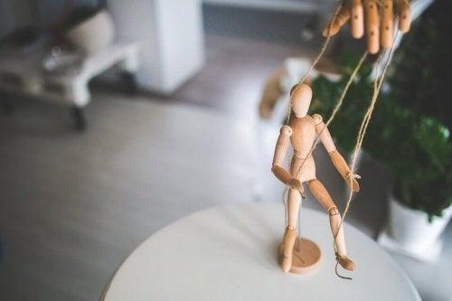 Eine Puppe, die durch eine Hand manipuliert wird