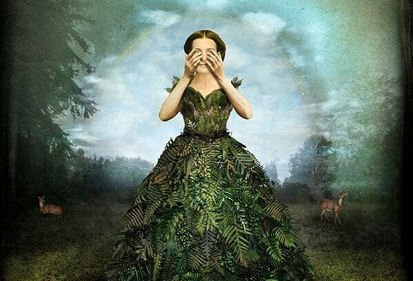 Frau in einem Blätterkleid verdeckt sich die Augen