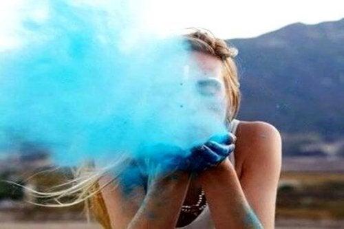 Frau mit einem gesunden Selbstwertgefühl bläst blauen Staub in die Kamera