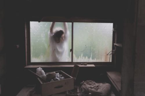 Frau steht am Fenster eines lange nicht aufgeräumten Zimmers