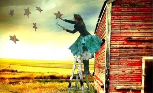 Frau, die auf einer Leiter steht, und Sterne am Himmel anbringt