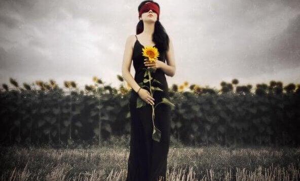 Frau mit Augenbinde und Sonnenblume