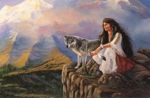 Frau sitzt neben einem Wolf auf einem Felsen