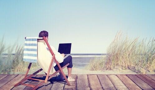 Mann sitzt im Liegestuhl am Strand