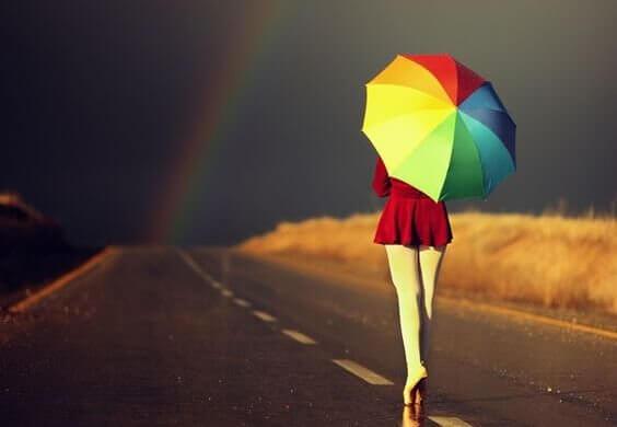 Mit buntem Regenschirm auf den dunklen Horizont zu