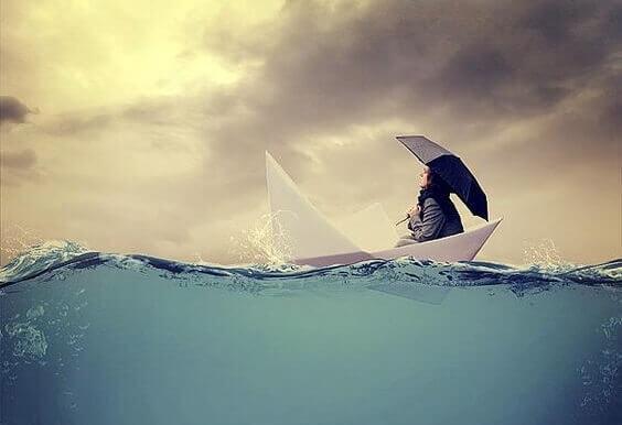 Frau sitzt in einem Papierschiff