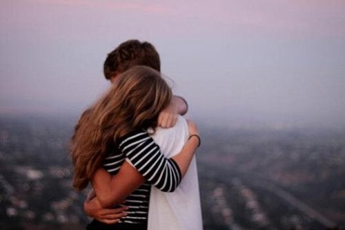 Paar umarmt sich vor städtischem Panorama