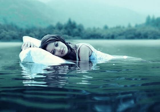 Frau auf Kopfkissen im See