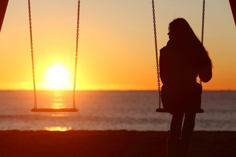 Frau sitzt auf Schaukel am Meer