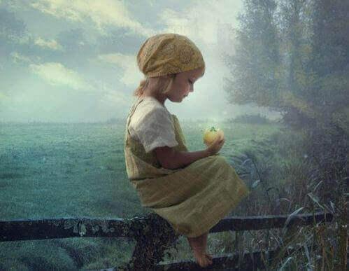 Mädchen auf einem Zaun hält einen gelben Apfel in der Hand
