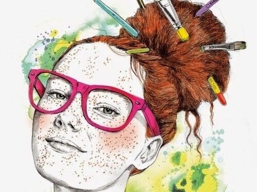 Kreative Frau mit Sommersprossen und rosa Brille