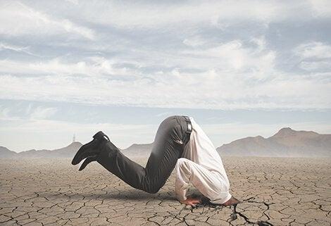 Mann steckt seinen Kopf in vertrockneten Boden