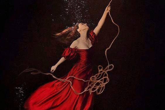 Frau wird an einem Seil nach oben gezogen