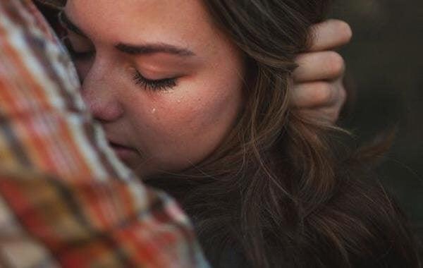 Rechtfertigen wir, wenn wir vergeben? - Frau weint in den Armen einer anderen Person