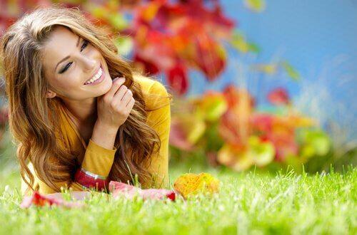 Frau liegt lächelnd auf der Wiese