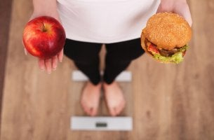 Eine Frau auf der Waage hält einen Apfel und einen Hamburger