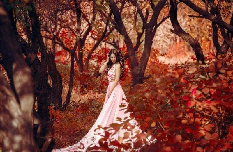Prinzessin mit rosa Kleid im Herbstwald