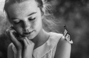 Ein Mädchen hat einen Schmetterling auf der Schulter