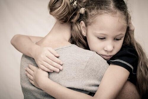 trauriges Mädchen, das ihre Mutter umarmt