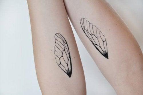 Arme mit Flügel-Tattoos