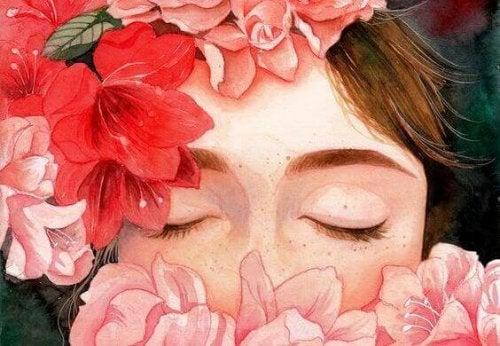 Frau mit geschlossenen Augen hinter Blumen